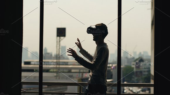 Silhouette of young man watching movie in VR headset and have virtual reality experience on hotel room balcony