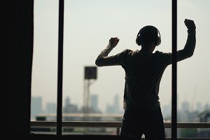 Silhouette of young man dancing ad listening music in wireles headphones stand on hotel room balcony