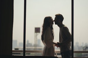 Young happy couple kissing and enjoying the view from a balcony overlooking city in morning during honeymoon