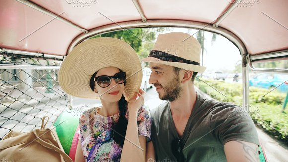 Young handsome man in hat with his girlfriend ride on traditional thai bus songteo. Couple travel Thailand during their honeymoon