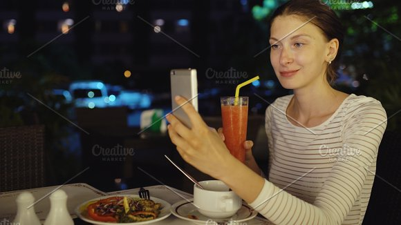 Happy woman shoot selfie using smartphone and drinck cocktail juice sitting in restaurant at night