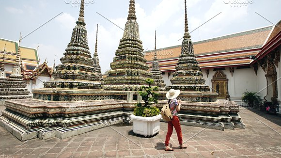 Young woman tourist taking pictures with smartphone at temple sightseeing in Bagnkok Thailand during traveling