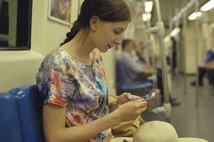 Young woman tourist travelling in subway and looking in map at smartphone in Bangkok subway during vacation