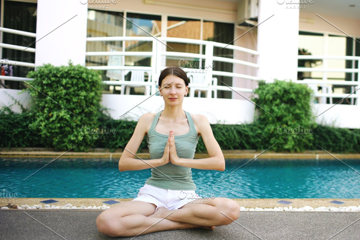 Calm woman doing yoga near swimming pool in hotel on sunny day