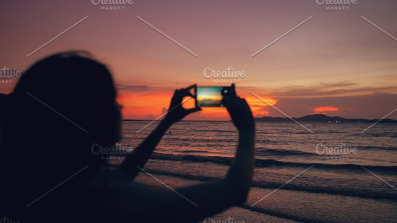 Closeup of young tourist woman photographs ocean view with smartphone during sunset at beach