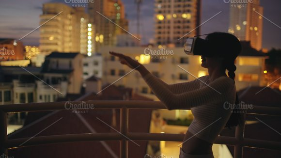 Young woman on rooftop terrace using virtual reality headset and having VR experience at night in Graphics