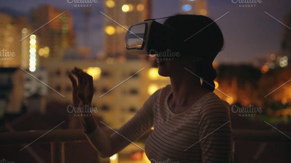 Young woman on rooftop terrace using virtual reality headset and having VR experience at night