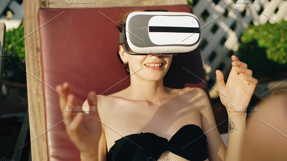 Young woman dressed in a glasses headset of virtual reality in hotel swimming pool