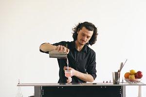 Professinal bartender man shaking cocktail at mobile bar table on white background