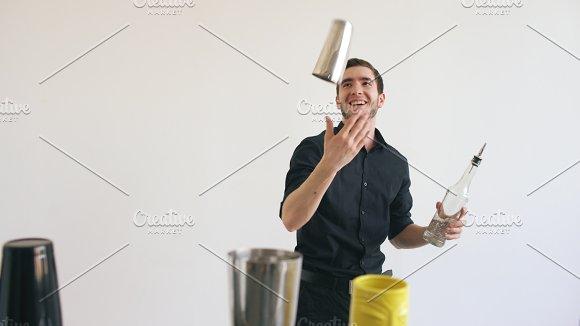 Professinal bartender man juggling bottles and shaking cocktail at mobile bar table on white background