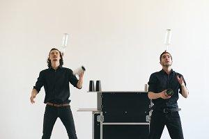 Professinal bartender men juggling bottles and shaking cocktail at mobile bar table on white background studio indoors