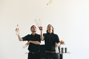 Professinal bartender men juggling bottles and shaking cocktail at mobile bar table on white background studio indoors