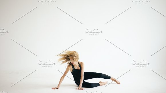 Modern beautiful teenage girl dancer dancing contemporary on white background indoors