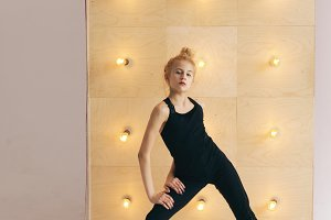 Young beautiful teenage girl dancer perfomance contemporary dance in ballroom on wall with lamps background indoors
