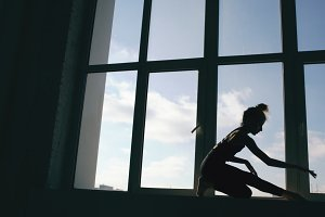 Silhouette of young girl dancer perfomance contemporary dance on windowsiil in dance studio indoors