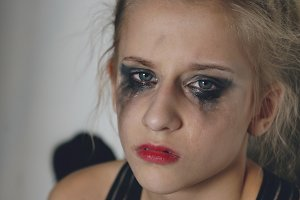 Closeup of young teenage girl dancer crying after loss perfomance sits on floor in hall indoors