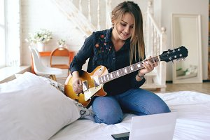 Attractive young girl learning to play electric guitar with notebook sit on bed in bedroom at home
