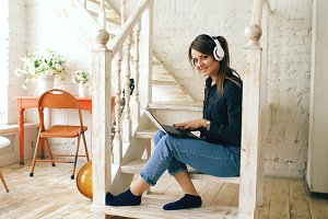 Beautiful woman with headphones and laptop posing and smiling while sitting on stairs at home