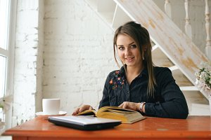 Young beautiful woman student posing and smiling read book at cafe indoors