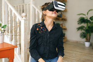 Woman in VR headset looking up and trying to touch objects in virtual reality at home indoors