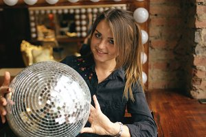 Beautiful young woman with disco ball posing and smiling in studio indoors