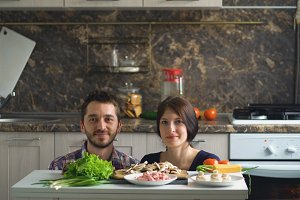 beautiful smiling couple above the table with vegetables while cooking in kitchen