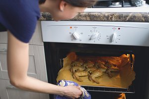 Housewife woman cook and check oven with roasted chicken wings in the kitchen at home