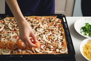 Young beautiful woman cook put tomatos on pizza dough in the kitchen at home
