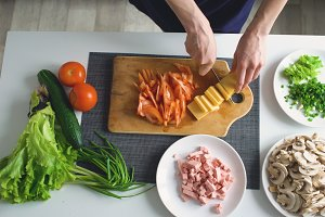Top view of woman hands cutting vegetables on a wooden board for pizza dinner in the kitchen at home