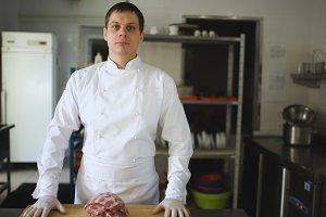 Professional chief cook posing before prepare steak dish at restaurant
