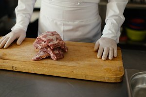 Closeup of professional chef prepare meat ribs on cutting board at restaurant kitchen