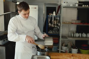 Professional chef man prepare gravy sauce with spices at restaurant kitchen