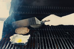 Closeup of chef preparing egg and cutlet for black burger on grill at restaurant kitchen indoors