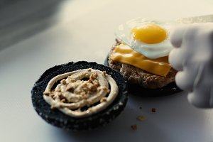 Closeup of chef cook grilled black burgerwith sauce and eggs on kitchen board