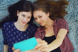 Top view of two pretty girls in pajamas making selfie portrait on bed in bedroom at home