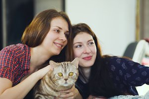 Two happy women friends lying in bed and making selfie with cat and have fun on bed at home