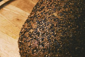 Black bread with seeds on dark background