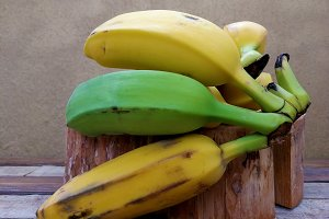 Green and yellow bananas on wood