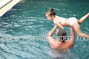 Happy family, active father with little child, adorable toddler daughter, having fun in swimming pool.