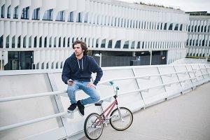 Male BMX rider on street with phone