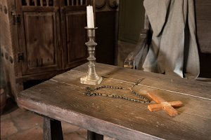 Ancient table with candle, rosary and cross in priest room