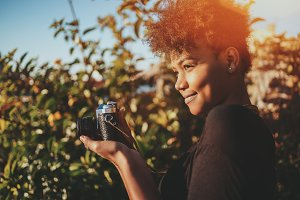 Biracial girl with retro photo cam