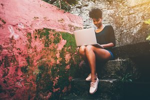 Girl with laptop sitting on stairs