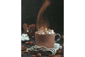 cinnamon powder flying over glass mug with hot chocolate