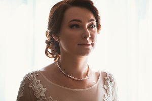 Portrait of a beautiful young bride near the window