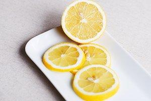 Slices of lemon on white plate. Food.