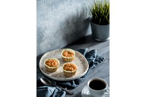 carrot muffins and coffee cup on gray wooden table
