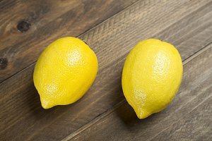 Two lemons on brown wooden table. Food