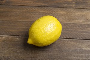 Lemon on brown wooden table. Food