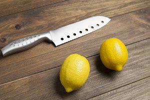 Lemons next to kitchen knife on brown wooden table.